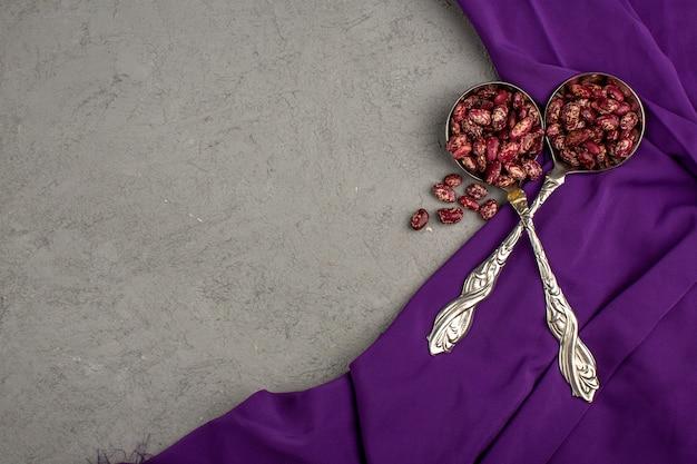 Maroon bohnen frisch in silbernen löffeln auf einem lila taschentuch und grauem boden