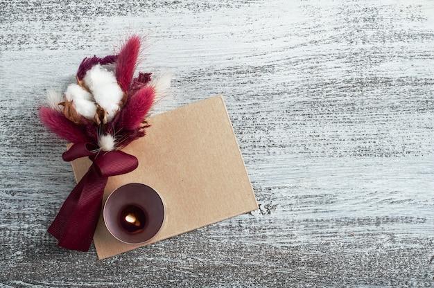 Marsala-strauß aus trockenen blumen und baumwolle am band mit brennender kerze. rustikaler backplatz für hochzeitskartenkonzept