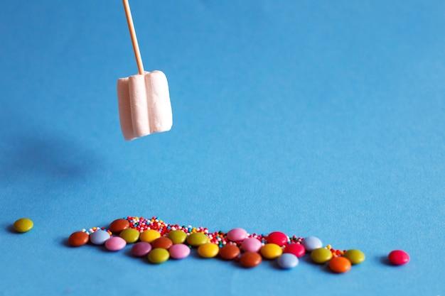 Marshmallow auf holzspieß mit farbbonbons auf blauem grund. urlaubskonzept.