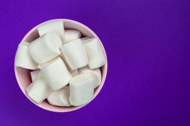Marshmallow auf violettem papier ausgelegt.