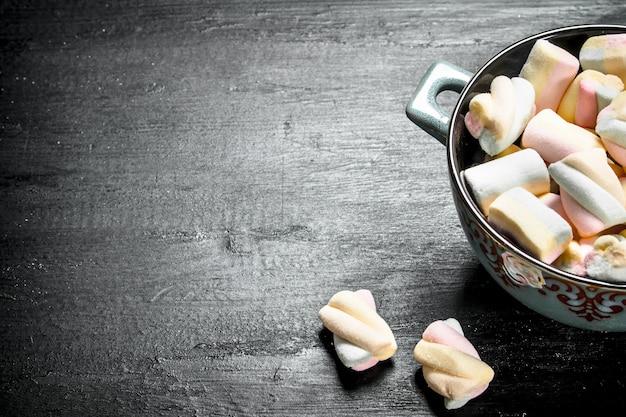 Marshmallow in einer schüssel. auf der schwarzen tafel.