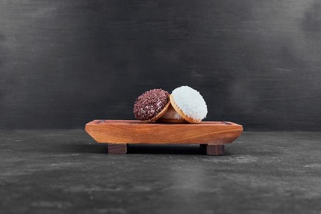 Marshmallow-kekse auf einer holzplatte auf schwarz