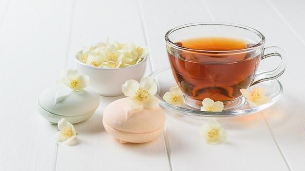 Marshmallow-makronen mit tee und jasminblüten auf einem weißen holztisch