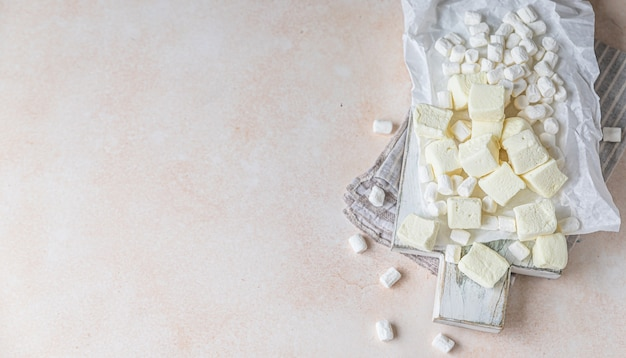 Marshmallow mit gelber quadratischer form und marshmallow mit weißer vanille auf holzschneidebrett