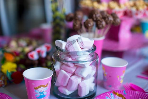 Marshmallow, süß gefärbte meringues, popcorn, puddingkuchen und cake pops auf dem tisch