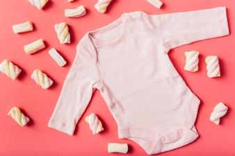 Marshmallow umgeben mit rosa Baby onesie auf Pfirsichhintergrund