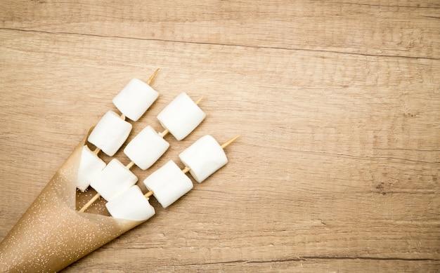 Marshmallows am spieß in einer papiertüte