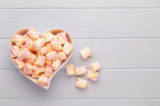 Marshmallows auf blauem hintergrund mit copyspace. flache lage oder draufsicht. hintergrund oder textur der bunten mini-marshmallows.