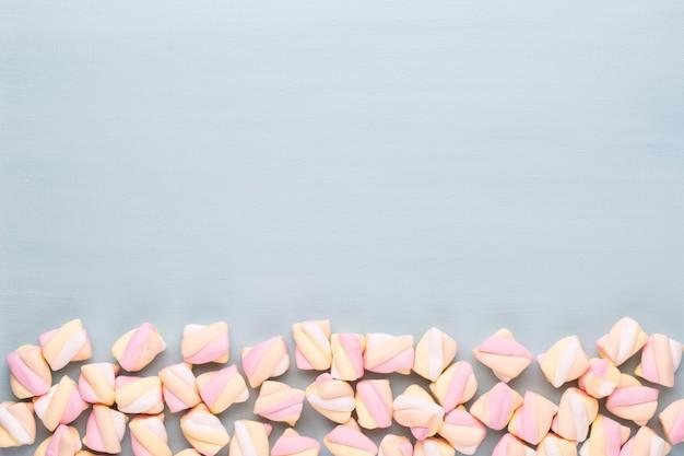 Marshmallows auf blauem hintergrund mit copyspace. flache lage oder draufsicht.