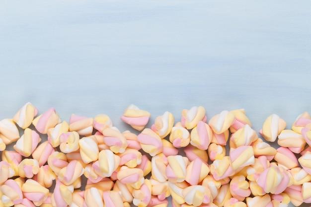 Marshmallows auf blauem tisch mit copyspace. flache lage oder draufsicht. hintergrund oder textur der bunten mini-marshmallows.