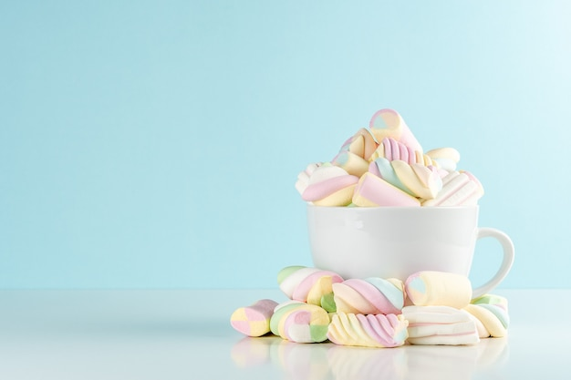 Marshmallows bunte kaubonbons in einer tasse auf blau.