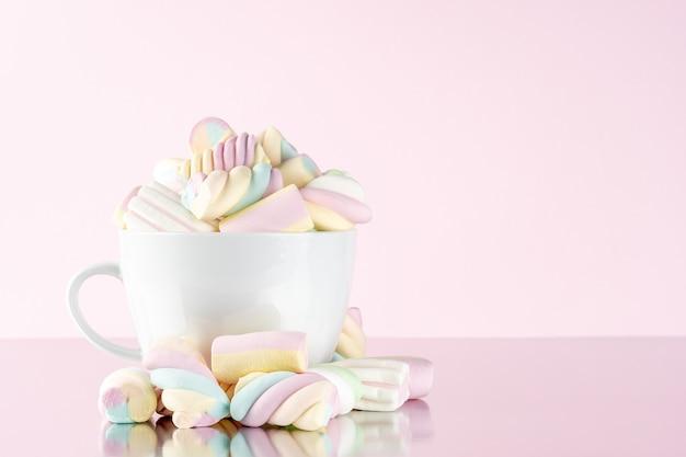 Marshmallows bunte kaubonbons in einer tasse auf rosa.