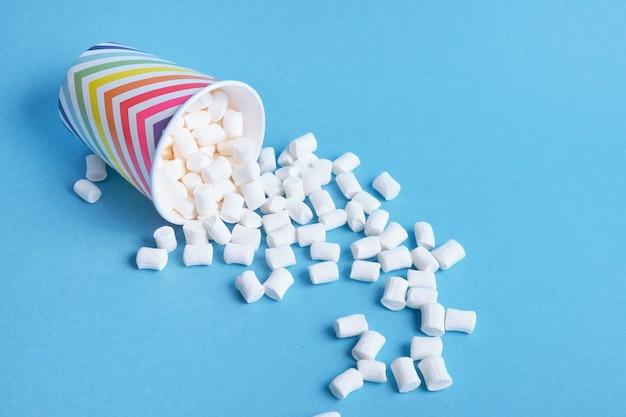Marshmallows fielen aus ihren weihnachtspapierbechern mit geometrischem muster auf blauem hintergrund, kopierraum