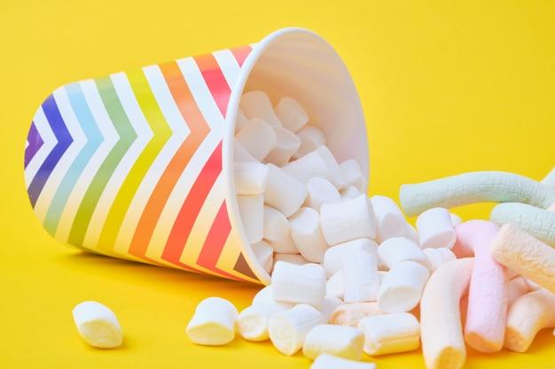 Marshmallows fielen aus ihren weihnachtspapierbechern mit geometrischen mustern auf gelbem hintergrund, kopienraum
