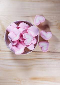 Marshmallows herz auf holz im vintage-ton