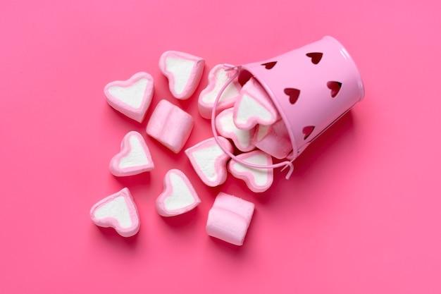 Marshmallows herz geformt verschüttet aus eisen bucketon rosa hintergrund