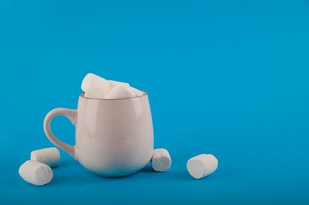 Marshmallows in einer tasse auf einer blauen raumnahaufnahme und kopieren raum. marshmallow in einer tassenmuster-draufsicht auf einem blauen raum.