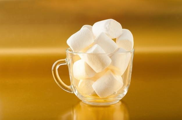 Marshmallows in einer tasse auf einer gelben nahaufnahme und kopierraum. marshmallow in einem durchsichtigen becher auf einem goldenen raum.