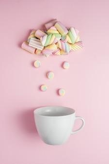 Marshmallows in form einer regnerischen wolke mit weißer tasse auf rosa.