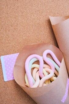 Marshmallows in form von spaghetti in geschenkpapier eingewickelt, korkhintergrund, umweltfreundliches lebensstilkonzept