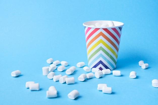 Marshmallows in papierferienglas mit geometrischem muster auf blauem hintergrund, kopierraum, marshmallows zum dekorieren von desserts und getränken