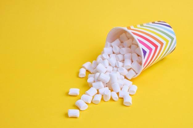 Marshmallows in papierferienglas mit geometrischem muster auf gelbem hintergrund