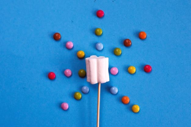 Marshmallows-komposition auf holzspießen auf blauem hintergrund. flache lage, urlaubskonzept. süßigkeiten in sonnenform