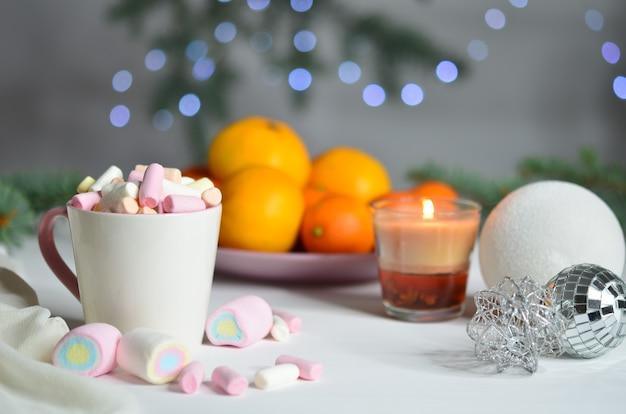 Marshmallows, mandarinen, kerze und weihnachtskugeln auf bokeh-hintergrund. neujahrsdekoration.