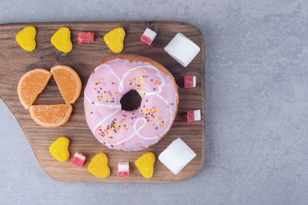 Marshmallows, marmeladen und ein donut auf einem holzbrett auf marmoroberfläche
