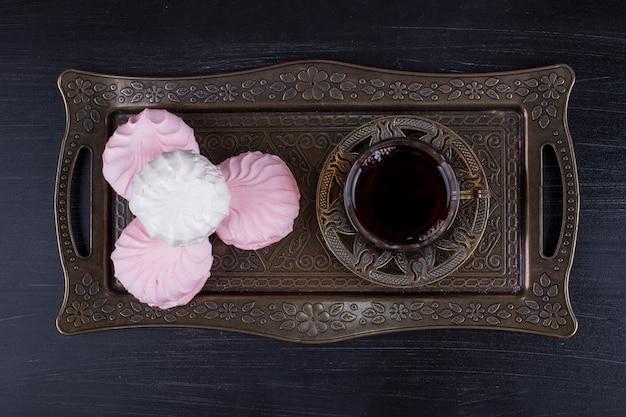 Marshmallows mit einem glas tee in einer metallplatte auf einer schwarzen oberfläche