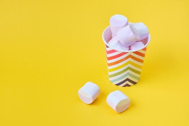 Marshmallows mit fruchtsaft in einem festlichen pappbecher mit geometrischem hellem muster auf gelbem hintergrund, kopierraum