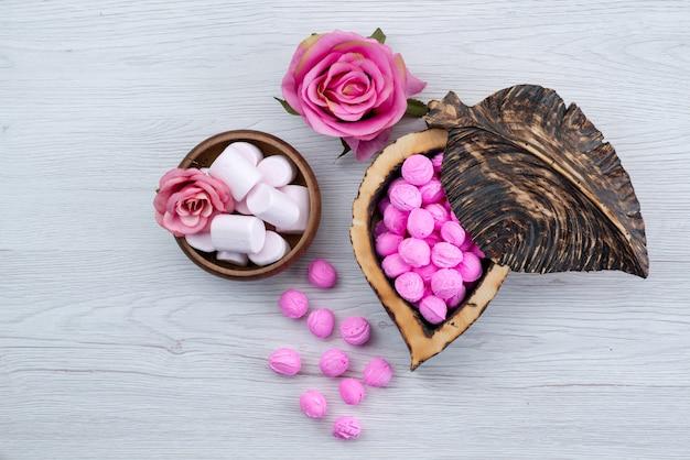 Marshmallows und bonbons der draufsicht lokalisiert auf weißer, zuckersüßer bonbonfarbe