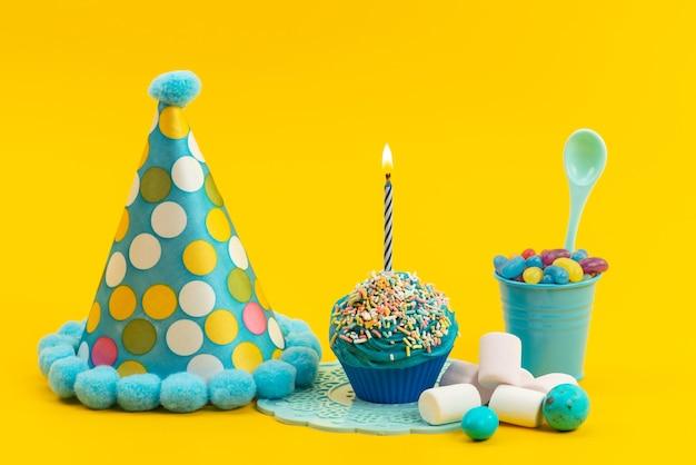 Marshmallows und bonbons der frotn-ansicht zusammen mit geburtstagskappenkuchen mit kerze auf gelbem schreibtisch, bonbonfarbengeburtstag