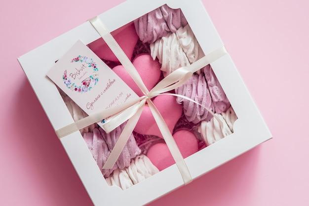 Marshmallows und makronen in einer geschenkbox mit platz für text