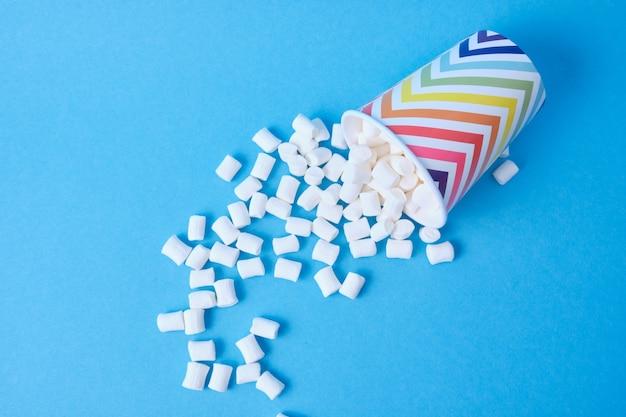 Marshmallows und pappbecher auf blauem hintergrund