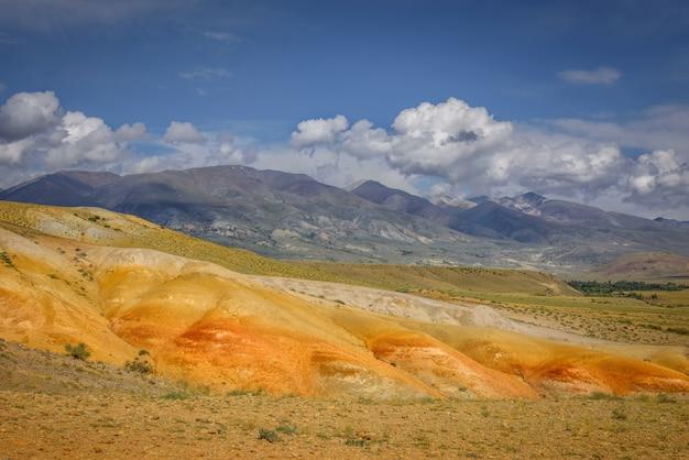 Marslandschaften in den altai-bergen, mehrfarbige felsen gegen einen blauen himmel mit weißen wolken