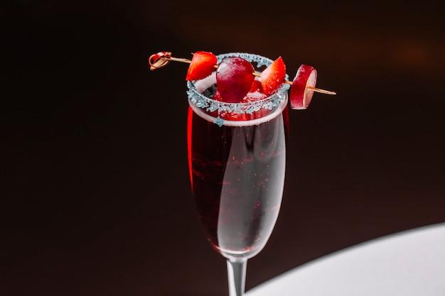 Martini-cocktail von der seite mit erdbeere und traube im champagnerglas