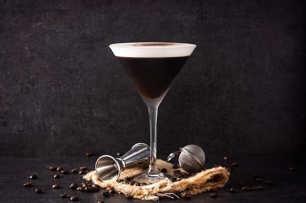 Martini-espressococktail im glas auf schwarzem hintergrund