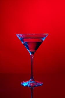 Martini glas auf rot mit blauem licht.