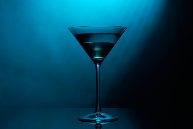 Martini-glas mit blauer farbe auf schwarz.