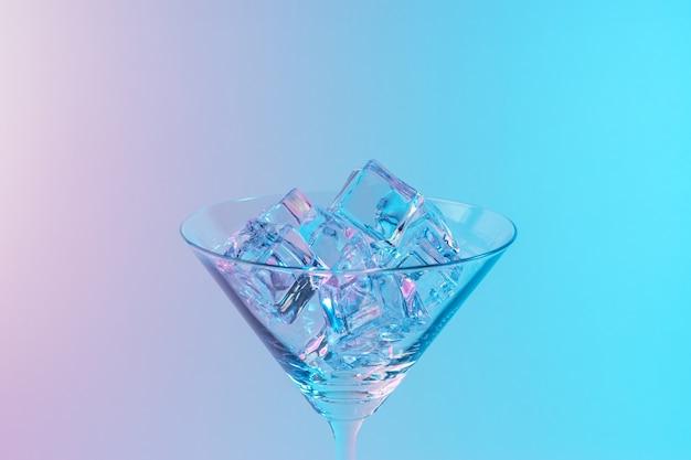 Martini-glas mit eiswürfeln in neonholographischen leuchtenden rosa und blauen farben