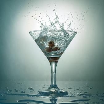 Martini glas mit spritzer und oliven