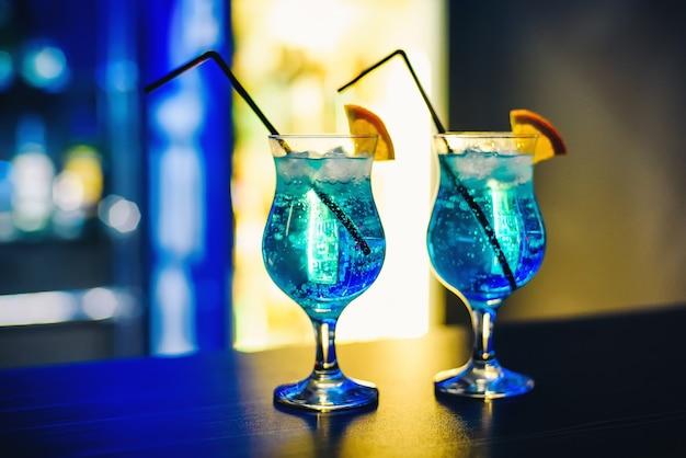 Martinis in gläsern mit eis auf der theke mit orange