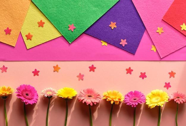 Marzipan-ostereier, gerberablumen, konfetti. geometrische anordnung.