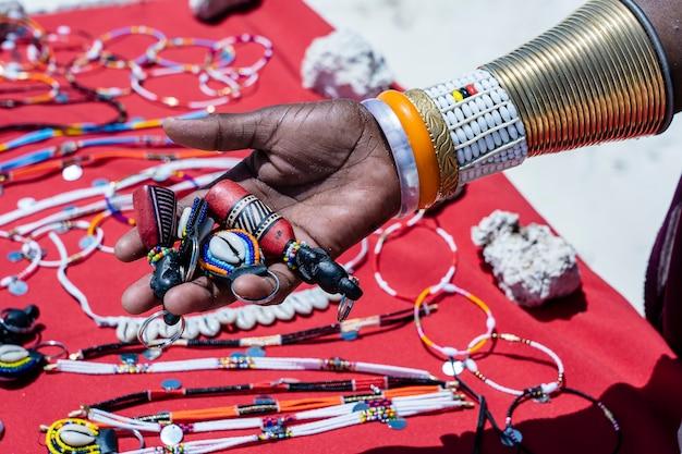 Masai stammes weibliche hand mit einem bunten armband hält souvenirs zum verkauf für touristen
