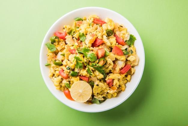 Masala anda bhurji oder würziges indisches rührei, beliebtes streetfood in mumbai. serviert in weißem geschirr, über stimmungsvollem hintergrund isoliert. selektiver fokus
