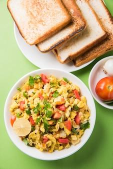 Masala anda bhurji oder würziges indisches rührei mit geröstetem brot oder brötchen oder pav, beliebtes streetfood in mumbai. serviert in weißem geschirr über stimmungsvollem hintergrund. selektiver fokus
