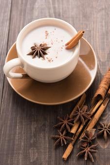 Masala-chai mit gewürzzimt, kardamom, ingwer, nelke und sternanis auf hölzernem hintergrund