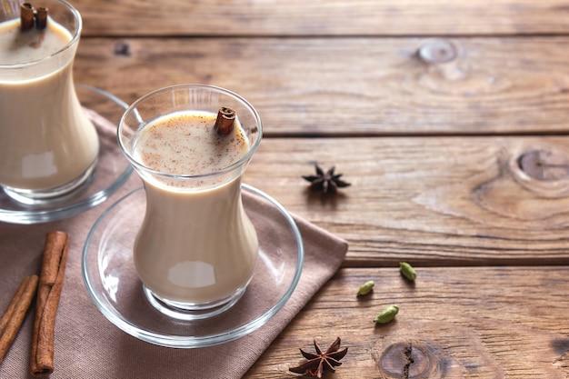 Masala chai mit zimt in den transparenten gläsern auf einem holztisch.