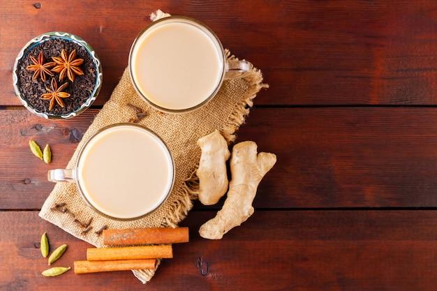 Masala chai tee auf sackleinen. traditionelles indisches getränk - masala-tee mit gewürzen auf einem hölzernen hintergrund.